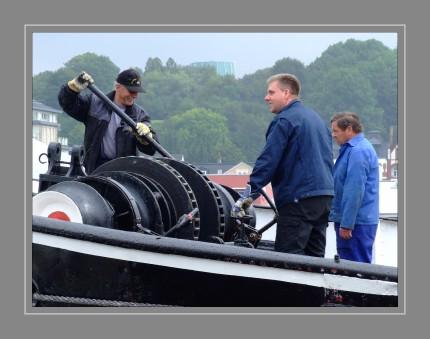 """Die Bussard ist weltweit der einzig noch fahrende Tonnenleger mit Dampfmaschine, ein Unikat unter den Speziallschiffen. Mit der Baunummer 203 wurde der Bussard im Jahre 1906 abgeliefert. Für dieses Spezialschiff mussten 224.000 Goldmark bezahlt werden, für jene Zeit eine stattliche Summe.  Als Bereisungs- und Versorgungsdampfer war der Bussard für das Feuerschiff """"Fehmarnbelt"""" im Einsatz. Dabei wurde Proviant, Wasser, Brenn- und Treibstoffe sowie Ersatzteile transportiert, auch das 14-tätige Auswechseln der Besatzungen war eine Aufgabe. Aber die Hauptaufgabe war das Auslegen, Einholen und Bergen von Tonnen. Die Tonnen wurden dann kontrolliert und wenn nötig auch an Bord instand gesetzt."""