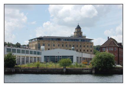 Die Walzenmühle Flensburg ist ein industrielles Kulturdenkmal von hohem städtebaulichen und besonderem architektur-geschichtlichem Wert. Anfang 2000 entstand die Idee, die Walzenmühle zu einem Medien- und Kulturwirtschaftszentrum mit ergänzenden Einzelhandels-, Wohn- und Büroflächen umzubauen Der Baustart wurde im Januar 2005 mit einem Spatenstich gefeiert. Im Februar 2007 wurde die Walzenmühle durch den damaligen Ministerpräsidenten  Carstensen eingeweiht.
